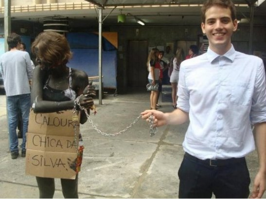 In 2013, in Belo Horizonte, a group of Law students participated in hazings of freshman; in this photo, a student is painted black, chained with a sign referring to a well-known Afro-Brazilian historical figure