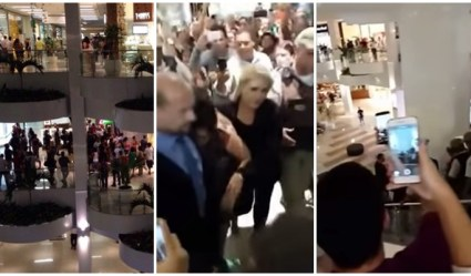 Photos shows crowd gathered outside of store, woman led out of store and witnesses recording the event