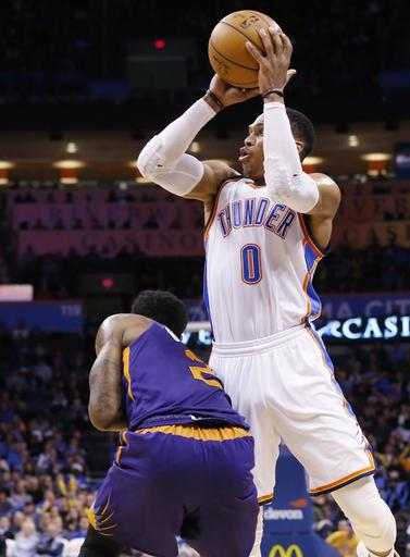 Oklahoma City Thunder guard Russell Westbrook (0) shoots per Phoenix Suns guard Eric Bledsoe (2) in the second quarter of an NBA basketball game in Oklahoma City, Saturday, Dec. 17, 2016. (AP Photo/Sue Ogrocki)