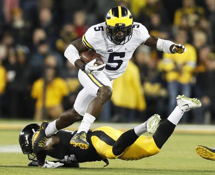 FILE - In this Nov. 12, 2016, file photo, Michigan's Jabrill Peppers (5) breaks a tackle by Iowa defensive back Desmond King, rear, during the first half of an NCAA college football game, in Iowa City, Iowa. Peppers was selected to the 2016 AP All-America college football team, Monday, Dec. 12, 2016. (AP Photo/Charlie Neibergall, File)