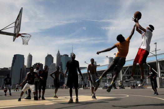 People play basketball under the skyline of lower Manhattan in Brooklyn Bridge Park in the Brooklyn borough of New York City, U.S., May 29, 2016.  REUTERS/Brendan McDermid