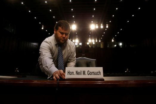 A U.S. Senate Judiciary Committee aide sets out a name plate at the seat of Supreme Court nominee judge Neil Gorsuch before the start of his confirmation hearing on Capitol Hill in Washington, U.S. March 20, 2017. REUTERS/Jonathan Ernst