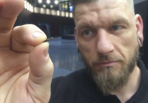 """Self-described """"body hacker"""" Jowan Osterlund from Biohax Sweden, holds a small microchip implant, similar to those implanted into workers at the Epicenter digital innovation business centre (Photo: James Brooks, AP)"""