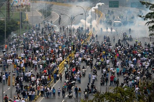 Police fired tear gas and rubber bullets to break up thousands of marchers as they reached a vital freeway in Caracas (AFP Photo/Federico PARRA)