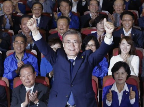 South Korea's presidential candidate Moon Jae-in of the Democratic Party raises his hands as his party leaders and members watch on television local media's results of exit polls for the presidential election in Seoul, South Korea, Tuesday, May 9, 2017. (Ahn Young-joon/Associated Press)