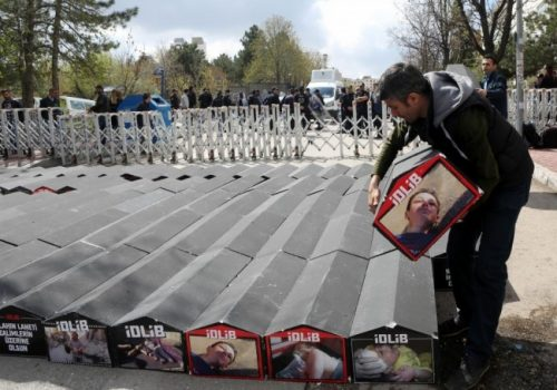 """A man carries one of the symbolic coffins with pictures of Syrian victims and inscriptions which translates as """"killer Assad"""" and """"killer Putin"""" set up during a protest against Russia for its alleged role in a chemical attack in the Syrian province of Idlib, on April 7 in Ankara. (Adem Altan/AFP/Getty Images)"""