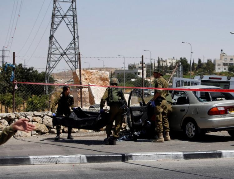Israeli soldiers remove the dead body of a Palestinian assailant at the scene of a car-ramming attack at the entrance of Beit Einun village, near the West Bank City of Hebron July 18, 2017. (Mussa Qawasma, Reuters)