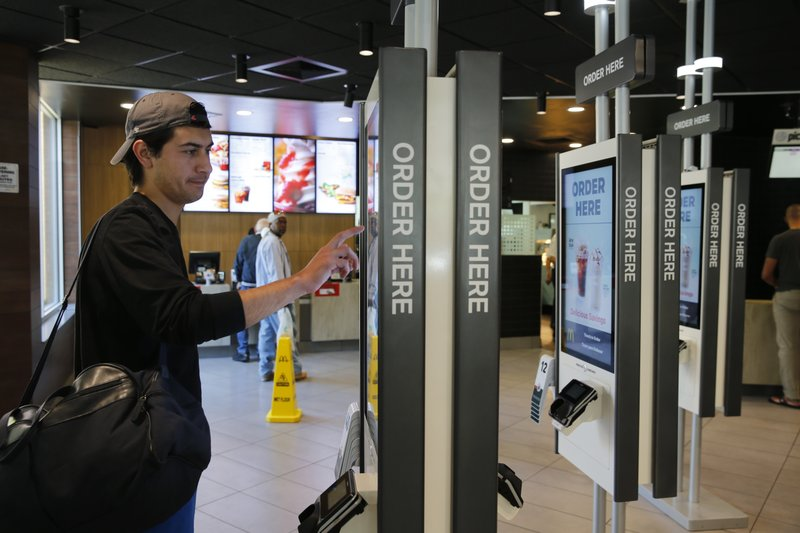 In this Thursday, June 1, 2017, photo, Brandon Alba from Milwaukee, orders food at a self-service kiosk at a McDonald's restaurant in Chicago. The company that helped define fast food is making supersized efforts to reverse its fading popularity and catch up to a landscape that has evolved around it. That includes expanding delivery, digital ordering kiosks in restaurants, and rolling out an app that saves precious seconds. (AP Photo/Charles Rex Arbogast)