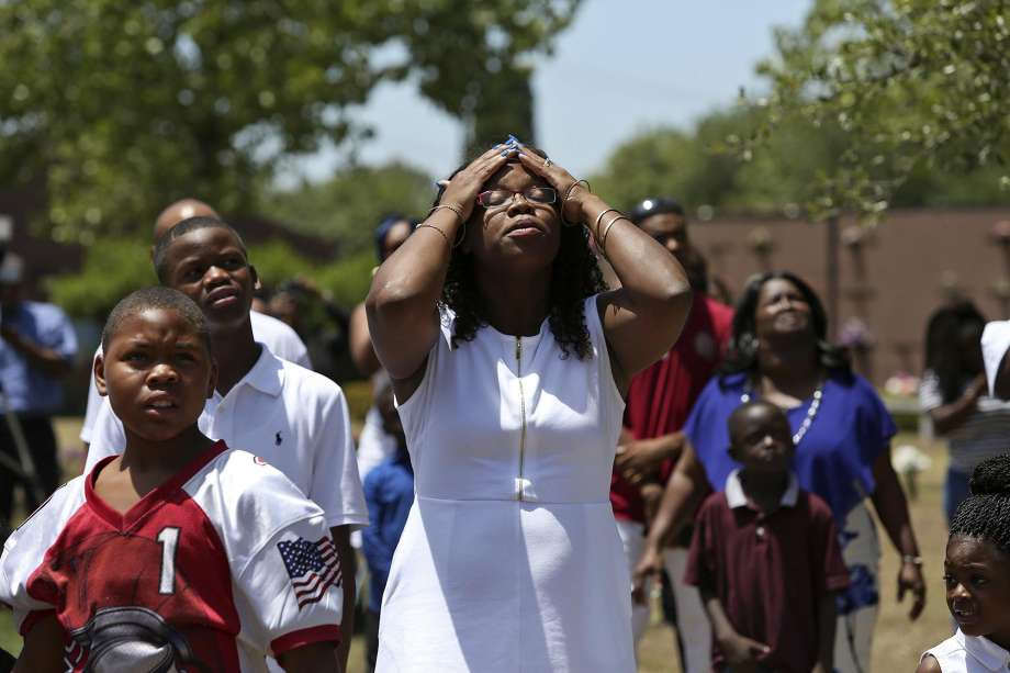 Cyntwanisha Whitley pauses after looking to the sky to watch balloons in the form of a Christian cross attached to a circle of blue balloons that she and family members released during the burial service.