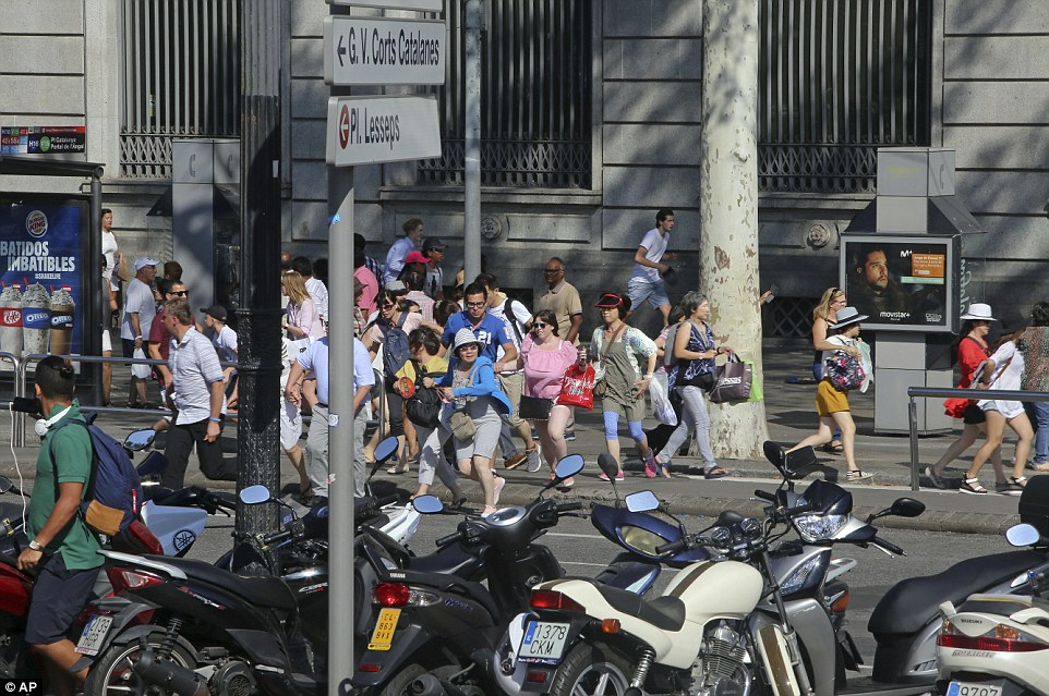 People flee after the van drove into crowds in the center of Barcelona.
