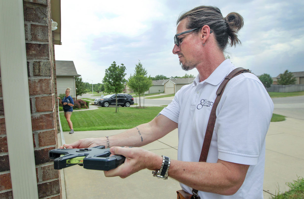 Redemption Church co-pastor Chad Gilstrap recently measured a home in north Wichita. He has a real estate appraising business with his wife Jennifer in addition to working at the church. (Fernando Salazar/Wichita Eagle/TNS)