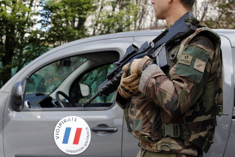 French soldier stands near the scene where French soldiers were hit and injured by a vehicle in the western Paris suburb of Levallois-Perret near Paris, France, Wednesday, Aug. 9, 2017. (Kamil Zihnioglu/Associated Press)