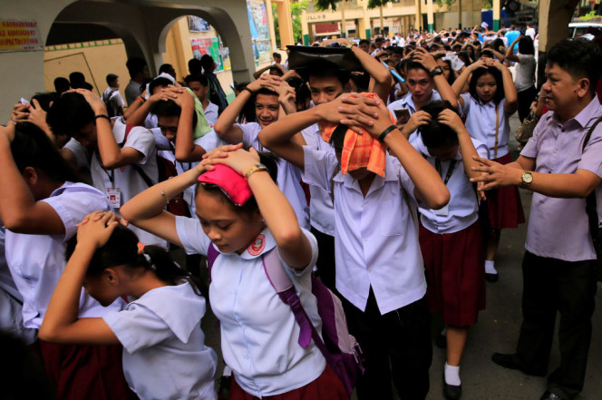 Students use their hands to cover their heads as they evacuate their school premises (Reuters)