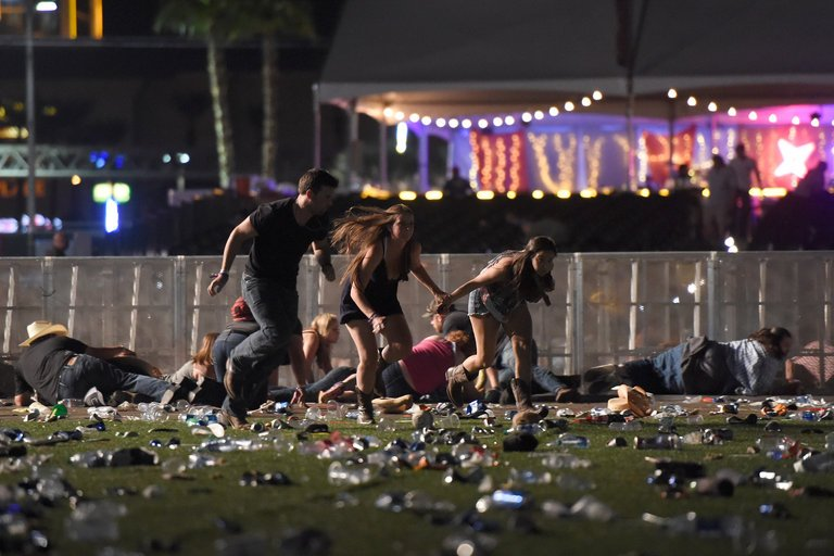 Running from the Route 91 Harvest country music festival near the Mandalay Bay Resort and Casino in Las Vegas after gunfire was heard on Sunday. (Credit: David Becker/Getty Images)