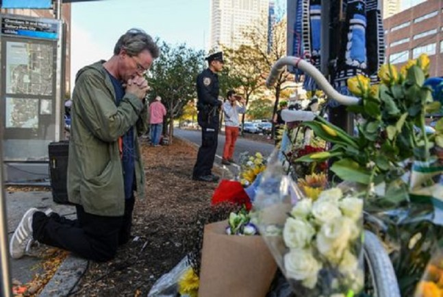 A man kneels down and prays at a memorial after the truck attack. (Photo by Ricky Carioti/The Washington Post)