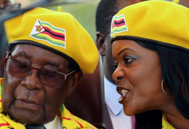 President Robert Mugabe listens to his wife Grace Mugabe at a rally of his ruling ZANU(PF) party in Harare, Zimbabwe, November 8, 2017. (PHOTO: REUTERS/PHILIMON BULAWAYO)