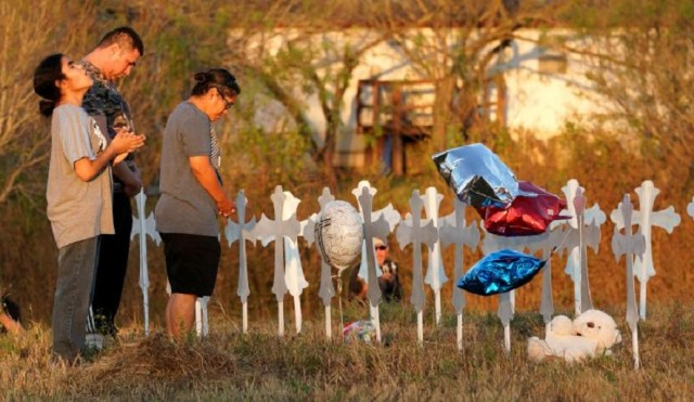 Miranda Hernandez (L) prays at sunset with father Kenneth and mother Irene at a row of crosses near the site of the shooting at the First Baptist Church of Sutherland, Texas. REUTERS/Rick Wilking