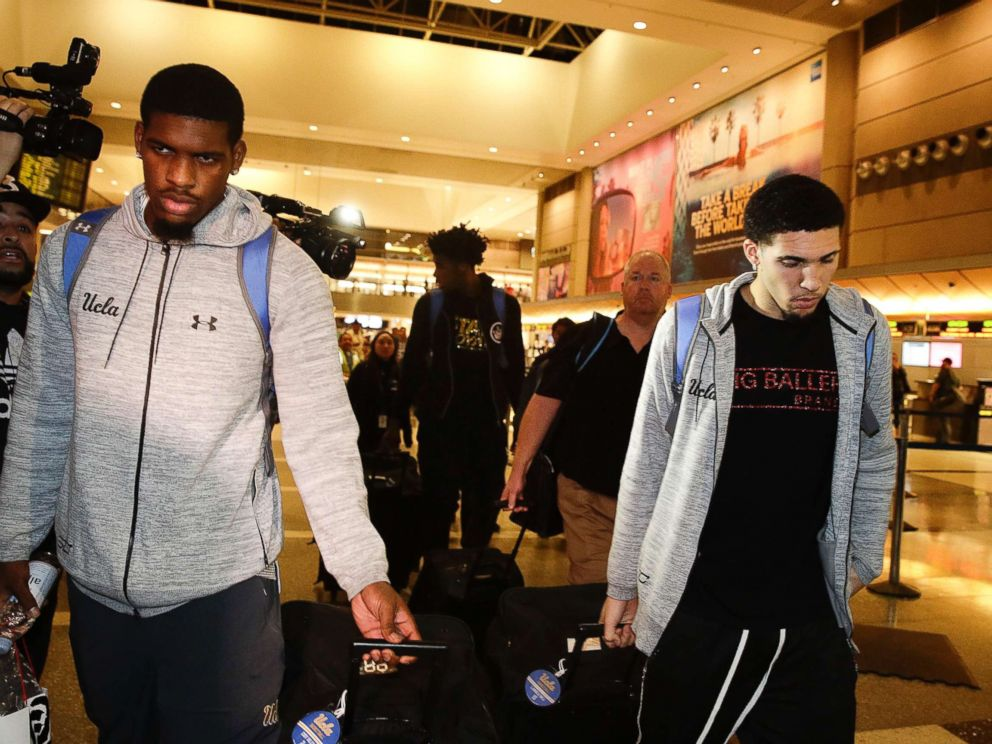 UCLA basketball players Cody Riley, left, LiAngelo Ball, right, and Jalen Hill, background center, are surrounded by the media as they leave the Los Angeles International Airport, Nov. 14, 2017, in Los Angeles.