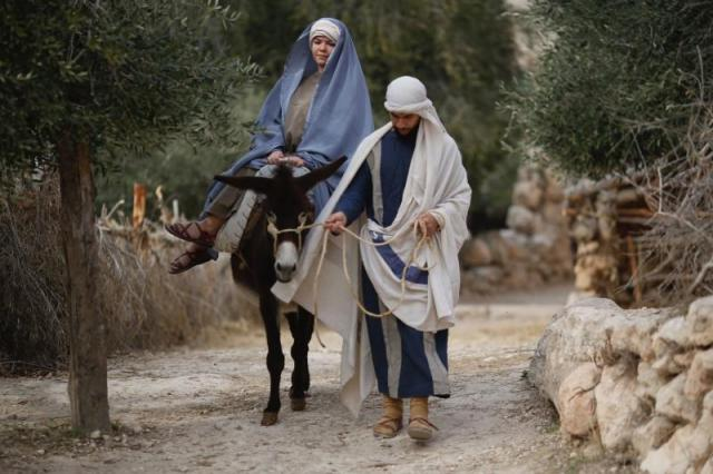 Christian actors portray Joseph and Mary during a re-enactment of a Nativity scene of the journey to Bethlehem as part of Christmas festivities at the Nazareth Village, northern Israel, Thursday, Dec. 21, 2017. (Ariel Schalit, AP)