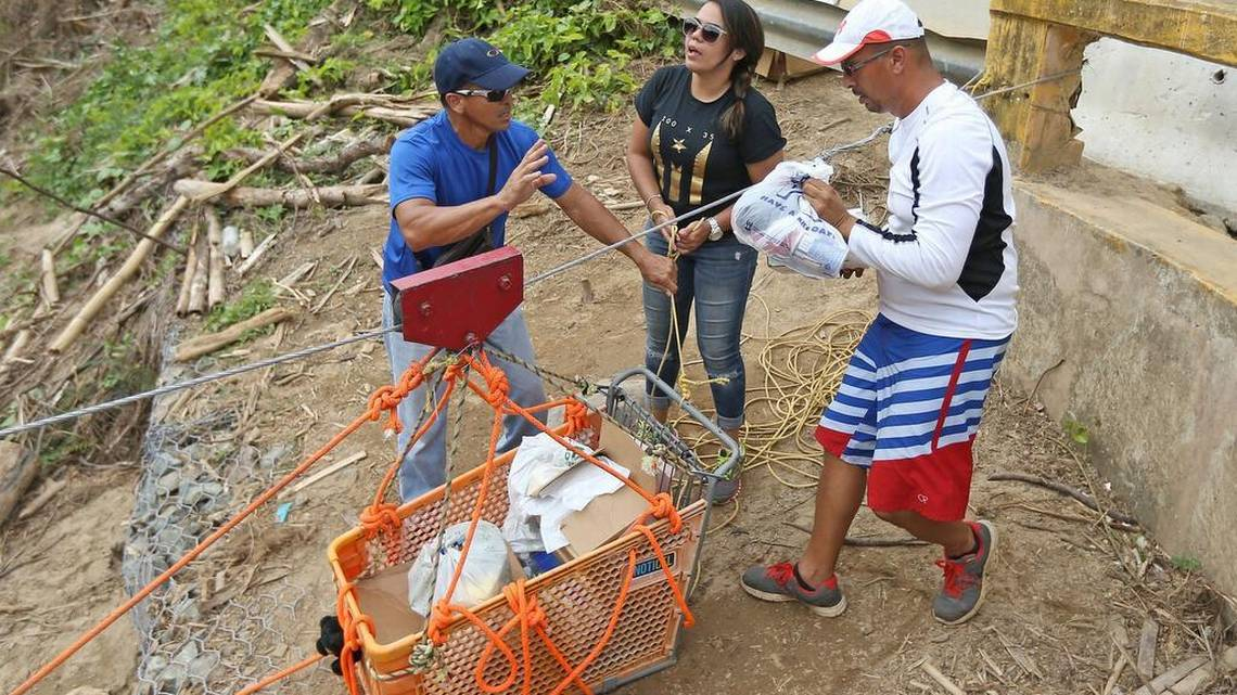Good Samaritans of the town of Isabela. Brothers Saul Aldarondo, left, and Luis Aldarondo, alongside Mary Lopez, fill a shopping cart with necessities for the Rio Abajo neighborhood of Utuado known now as 'The Forgotten Ones' during the aftermath of Hurricane Maria. (David Santiago, Miami Herald)
