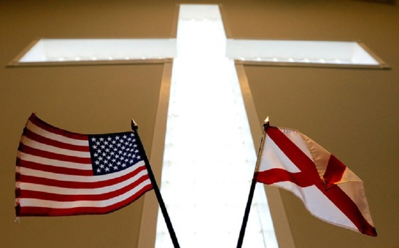 The American and Alabama state flags are displayed beneath a cross inside the church where Alabama Supreme Court Chief Justice, Roy Moore, spoke to the congregation of Kimberly Church of God on Sunday, June 28, 2015, in Kimberley, Ala. (AP Photo/Butch Dill)