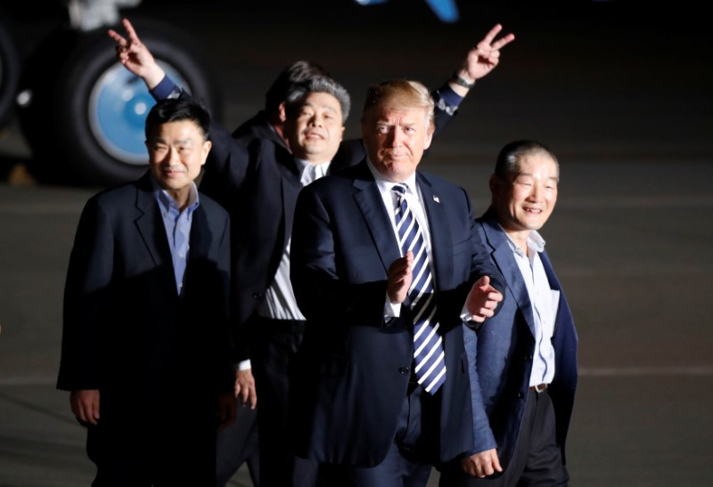 The three Americans formerly held hostage in North Korea gesture next to U.S.President Donald Trump, upon their arrival at Joint Base Andrews, Maryland, U.S., May 10, 2018.  REUTERS/Jim Bourg