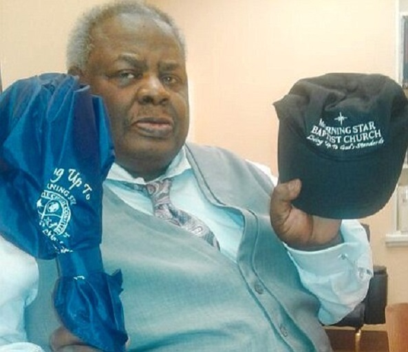 Rev. Ernest Blue holding up  the umbrella and cap he received from Richmond's Morning Star Baptist Church instead of a $100 honorarium.