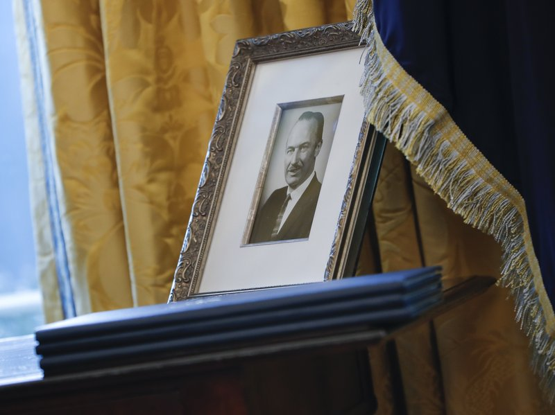 FILE - In this Feb. 9, 2017, file photo, a portrait of President Donald Trump's father Fred Trump, and three un-signed Executive orders are seen in the Oval Office of the White House in Washington. The New York Times is reporting that President Donald Trump received at least $413 million from his father over the decades, much of that through dubious tax dodges, including outright fraud. (AP Photo/Pablo Martinez Monsivais, File)