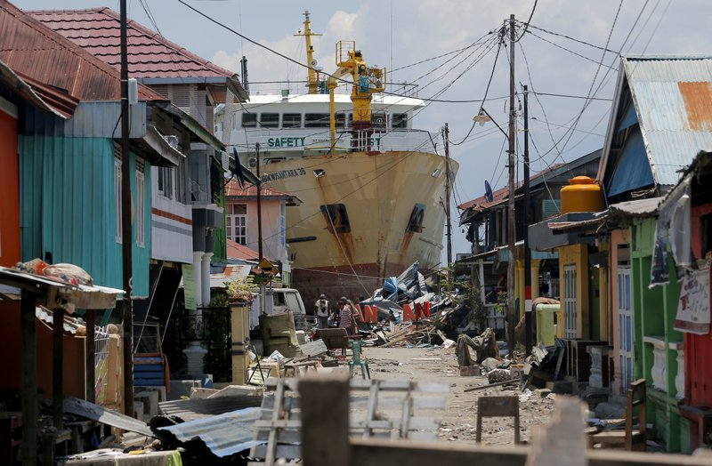FILE - In this Tuesday, Oct. 2, 2018, file photo, a ship rests near houses after it was swept ashore during Friday's tsunami at a neighborhood in Donggala, Central Sulawesi, Indonesia. Five days after Indonesia's earthquake and tsunami devastated villages on Sulawesi island, residents hoping that help would soon arrive are angry because it hasn't. (AP Photo/Tatan Syuflana, File)
