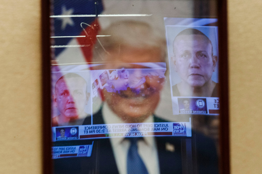 TV news coverage is reflected in the portrait of President Trump, showing the mail bomb suspect Cesar Sayoc Jr., at the Department of Justice in Washington on Friday. (Credit: Shawn Thew/Epa-Efe, via Rex)