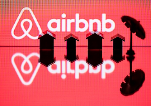 This illustration picture taken in Paris on August 29, 2018, shows  a toy umbella and houses next to the logo of  rental website Airbnb. (Photo by JOEL SAGET / AFP)