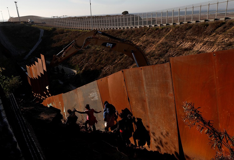 Migrants, part of a caravan of thousands from Central America trying to reach the United States, climb down a steep hill after giving up on trying to climb the border wall into the U.S. from Tijuana, Mexico, on December 13, 2018. (Leah Millis / Reuters)