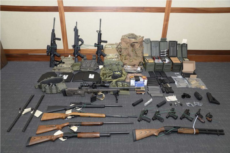 """This image provided by the U.S. District Court in Maryland shows a photo of firearms and ammunition that was in the motion for detention pending trial in the case against Christopher Paul Hasson. Prosecutors say that Hasson, a Coast Guard lieutenant is a """"domestic terrorist"""" who wrote about biological attacks and had a hit list that included prominent Democrats and media figures. He is due in court on Feb. 21 in Maryland. Prosecutors say Hasson espoused extremist views for years. Court papers say Hasson described an """"interesting idea"""" in a 2017 draft email that included """"biological attacks followed by attack on food supply."""" (U.S. District Court via AP)"""