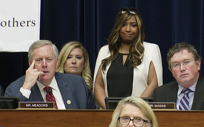 """In this image made from a Wednesday, Feb. 27, 2019, video, Rep. Mark Meadows, R-N.C., listens as he questions Michael Cohen, President Donald Trump's former lawyer, as Cohen testifies before the House Oversight and Reform Committee on Capitol Hill in Washington. Lynne Patton, who works in the Trump administration at the Department of Housing and Urban Development, stands behind Meadows, as Meadows said to Cohen, """"I asked Lynne to come today in her personal capacity to actually shed some light."""" (AP Photo)"""