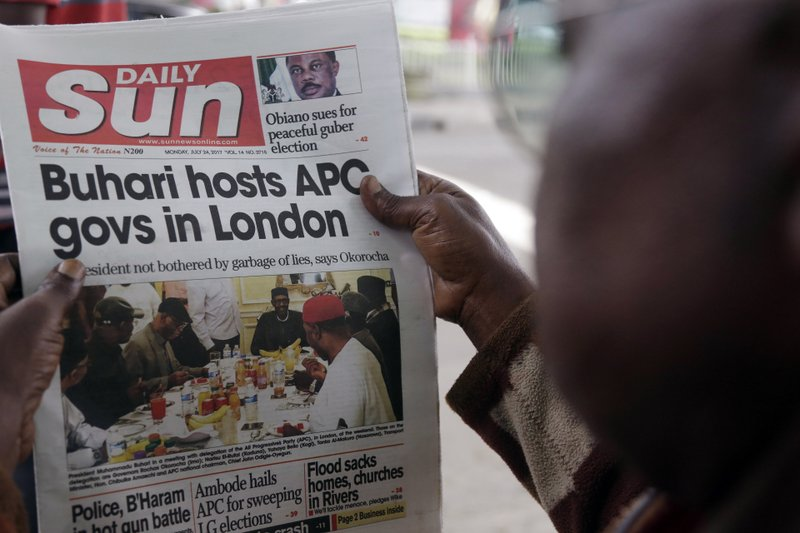 FILE - In this Monday, July. 24, 2017 file photo, a man reads a story about Nigeria's President Muhammadu Buhari after the government released a photo of Buhari more than two months after he left for London for medical treatment, in Lagos, Nigeria. In Nigeria and other African countries fighting fake news is vexing and divisive, especially as major elections loom. (AP Photo/Sunday Alamba, File)