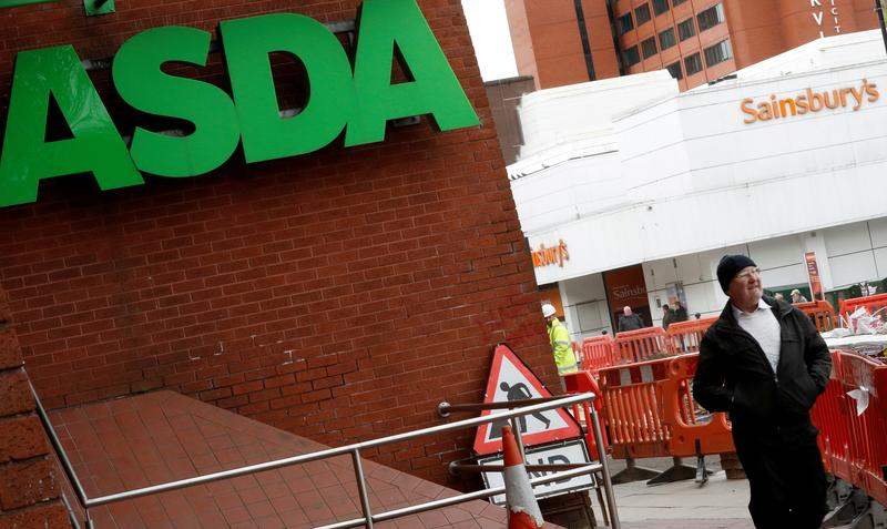 FILE PHOTO: A man walks past branches of ASDA and Sainsbury's in Stockport, Britain April 30, 2018. REUTERS/Phil Noble/File Photo