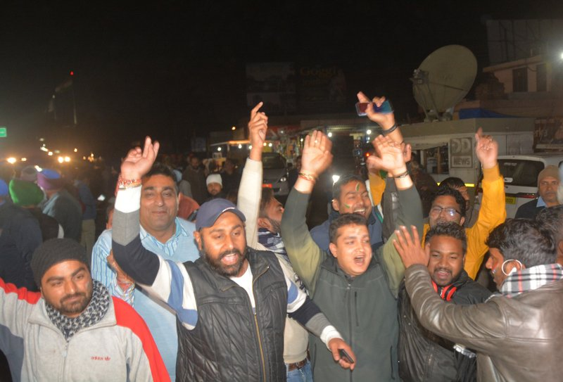 """Indians celebrate after the convoy carrying Indian air force Wing Commander Abhinandan Varthaman entered the Indian side of the border in Attari, India, Friday, March 1, 2019. Pakistani officials handed over the captured Indian pilot to a border crossing with India on Friday in a """"gesture of peace"""" promised by Pakistani Prime Minister Imran Khan amid a dramatic escalation with the country's archrival over the disputed region of Kashmir. (AP Photo/Prabhjot Gill)"""