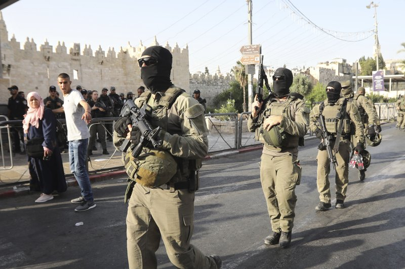 Israeli border police officers walk near the scene of a stabbing attack outside the Damascus Gate in Jerusalem's Old City, Friday, May 31, 2019. The incident occurred just hours before weekly Friday prayers at the nearby Al-Aqsa Mosque, when tens of thousands of people are expected for Ramadan prayers. (AP Photo/Mahmoud Illean)