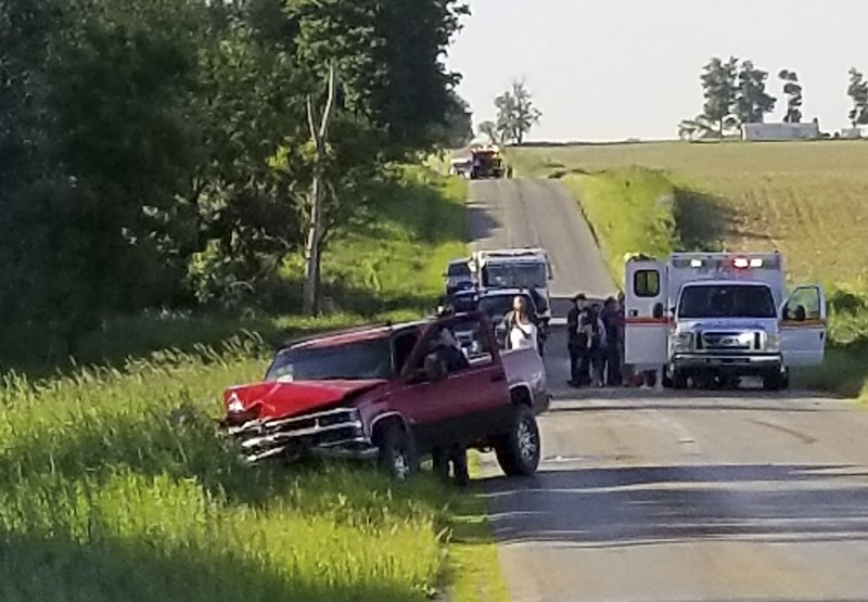A damaged truck sits on the side of the road after an accident involving a horse-drawn carriage on Friday, June 7, 2019 in California Township, Mich. Michigan State Police said the pick up truck was headed southbound when the driver rear ended an Amish, horse-drawn carriage. Two adults and five children were ejected from the carriage. (Don Reid/The Daily Reporter via AP)
