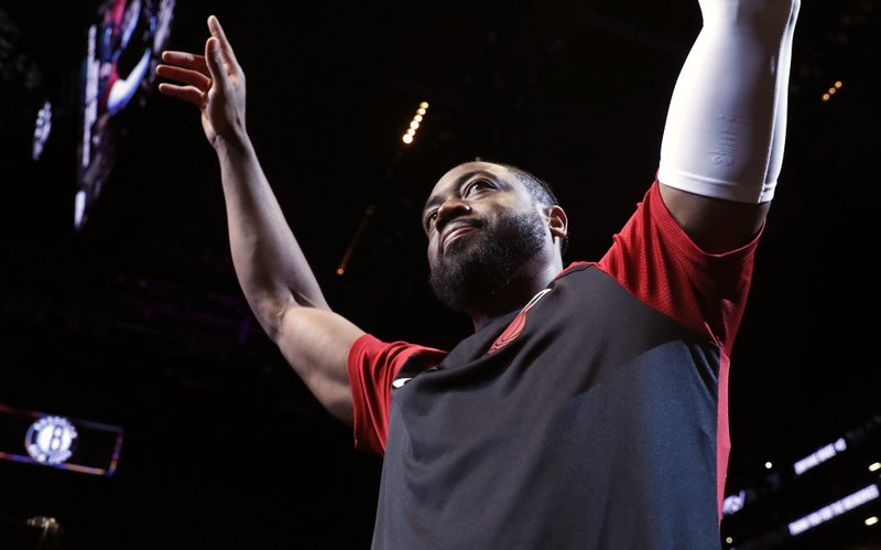 """FILE - In this Wednesday, April 10, 2019, file photo, Miami Heat guard Dwyane Wade (3) acknowledges cheers from the crowd before the start of the final NBA basketball game of his career, against the Brooklyn Nets in New York. William Morrow announced Wednesday, June 5, 2019, that Wade, who retired at the end of the 2018-2019 season, has a memoir coming out called """"3 Dimensional,"""" scheduled for release in October. (AP Photo/Kathy Willens, File)"""