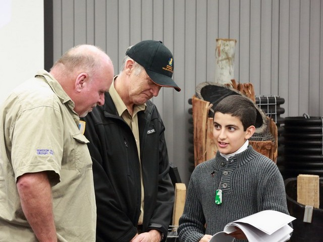 boy speaking enthusiastically to wildlife officers