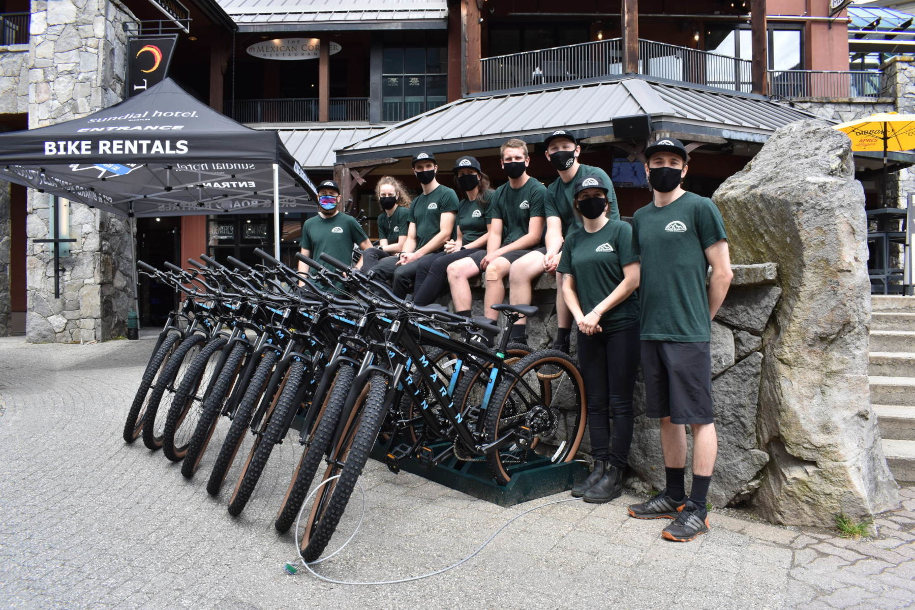 Staff sat on the wall next to bikes.
