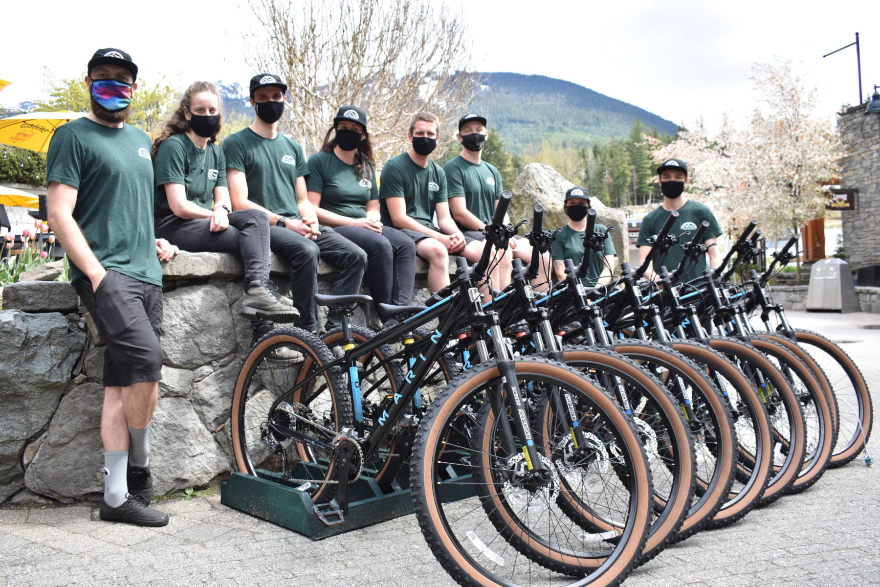 Staff photo with bikes and view of Whistler mountain.