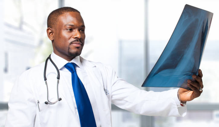 African American doctor looking at lung x-ray