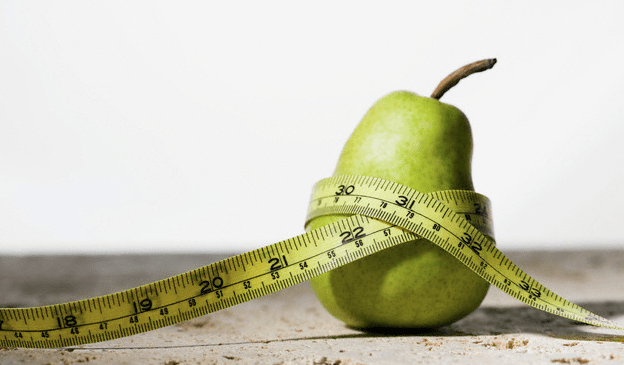 A pear wrapped with a yellow tape measure