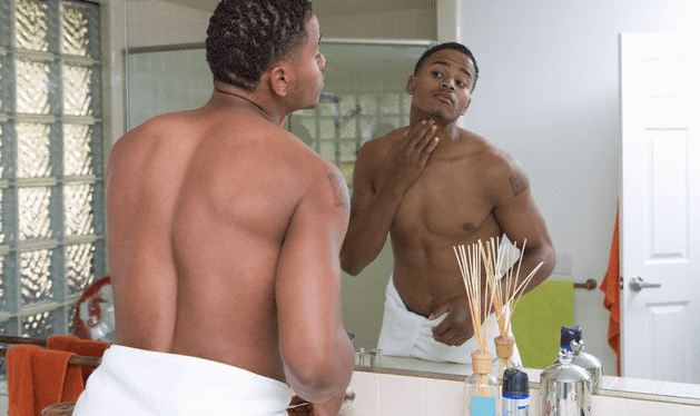 A man touching his skin and looking in the mirror