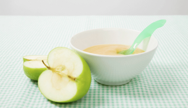 Half of an apple and a bowl of applesauce
