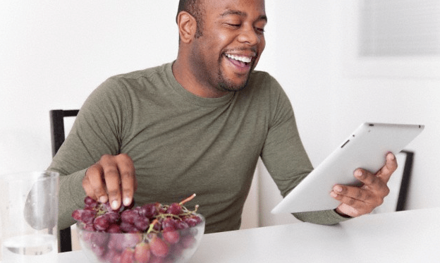 A man eating grapes and reading his iPad