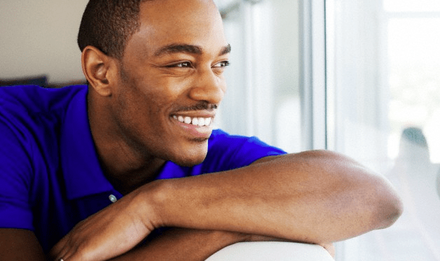 A man in a blue shirt smiling as he looks out a window