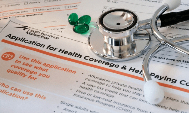 An application for health insurance, a stethoscope and some pills